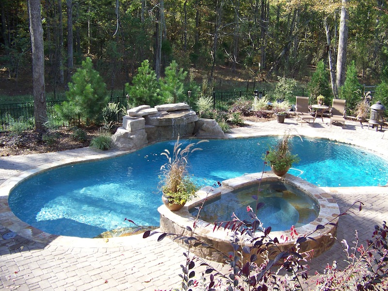 freeform swimming pool with grotto and deck pavers